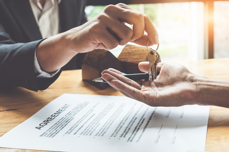 Estate agent giving house keys to customer and sign agreement in office.